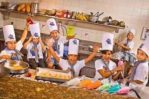 Picture of group of kids having a cookie decorating class at a resort.