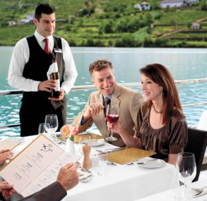Picture of steward offering wine to diners eating outside on a river boat cruise