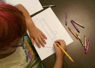picture of a child drawing a cruise ship for her journal.